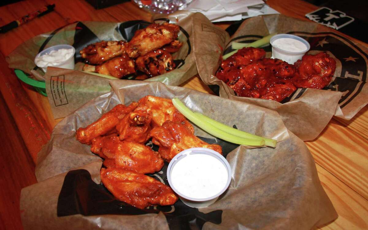 A collection of Buffalo wings at Charlie Brown's Neighborhood Bar & Grill includes (clockwise from top left) grilled spicy plum, cherry chipotle and traditional hot sauce.
