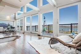 The living room at 21 Filbert Court in Sausalito opens to a wood deck overlooking the water.