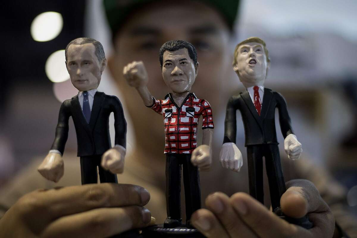 Model toy maker Dennis Mendoza shows miniature dolls of Russian President Vladimir Putin (L), Philippine President Rodrigo Duterte (C) and US President Donald Trump at the TOYCON 2018, Philippine toys, hobbies and collectibles convention in Manila on June 8, 2018. / AFP PHOTO / NOEL CELISNOEL CELIS/AFP/Getty Images