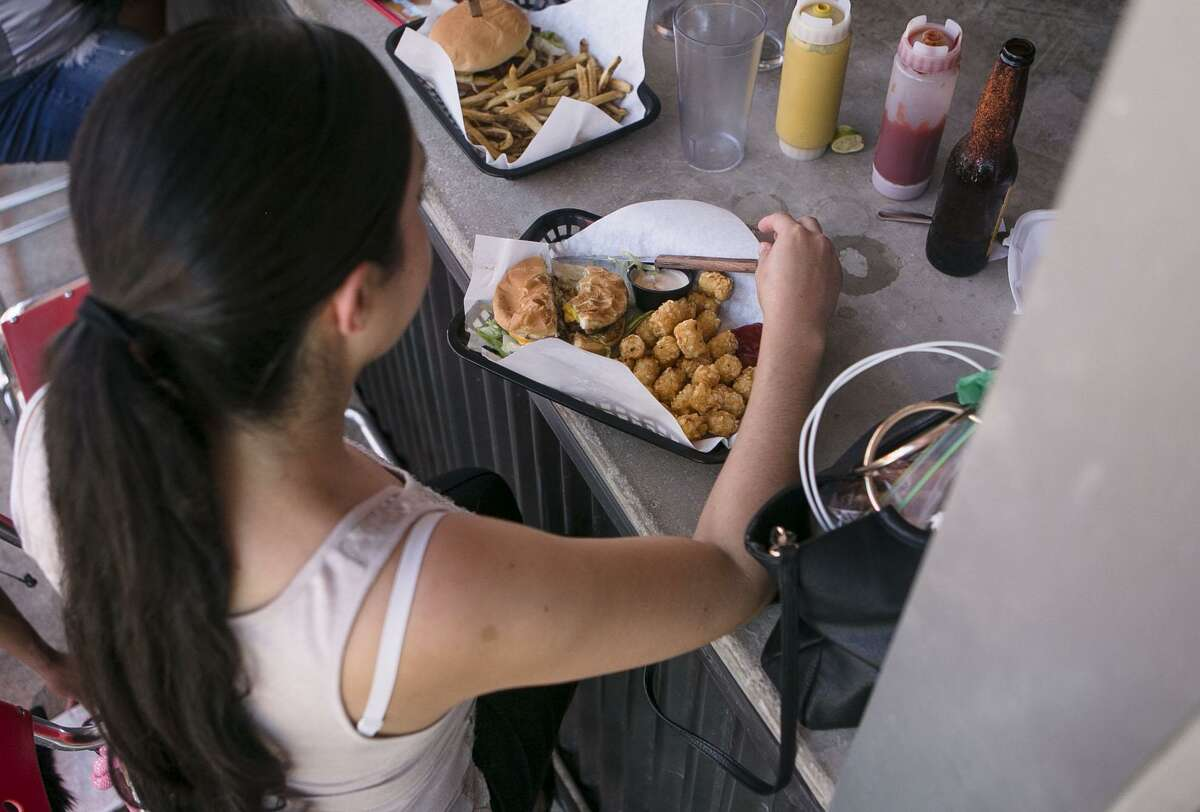 Rose Segura prepares to dig into her burger and tater tots at Luther's Cafe in San Antonio. Luther's Cafe is the winner of the San Antonio Express-News Readers' Choice of LGBTQ-Friendly Bar/Cafe.