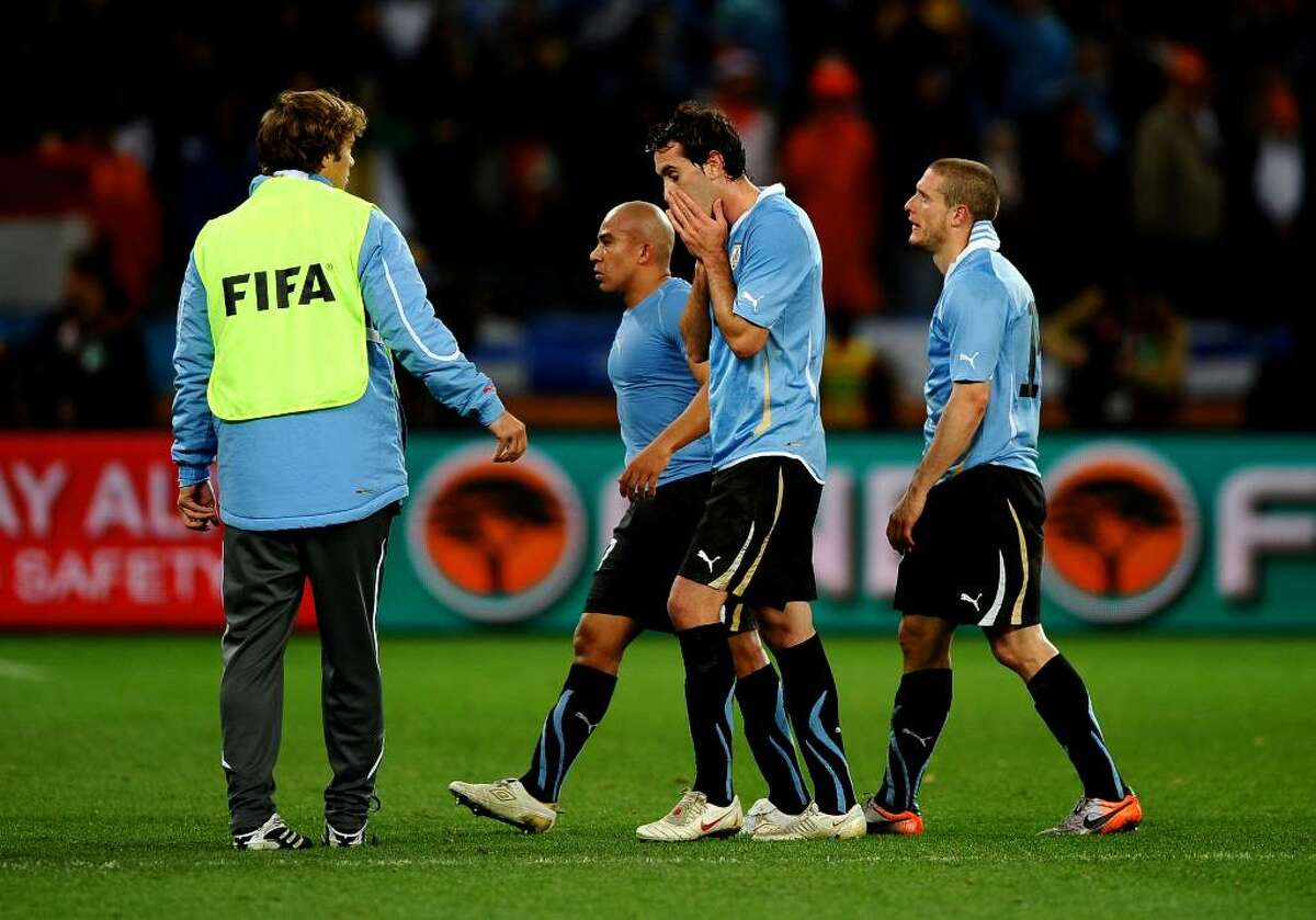 CAPE TOWN, SOUTH AFRICA - JULY 06: The Uruguay team leave the field dejected after suffering defeat in the 2010 FIFA World Cup South Africa Semi Final match between Uruguay and the Netherlands at Green Point Stadium on July 6, 2010 in Cape Town, South Africa. (Photo by Laurence Griffiths/Getty Images)