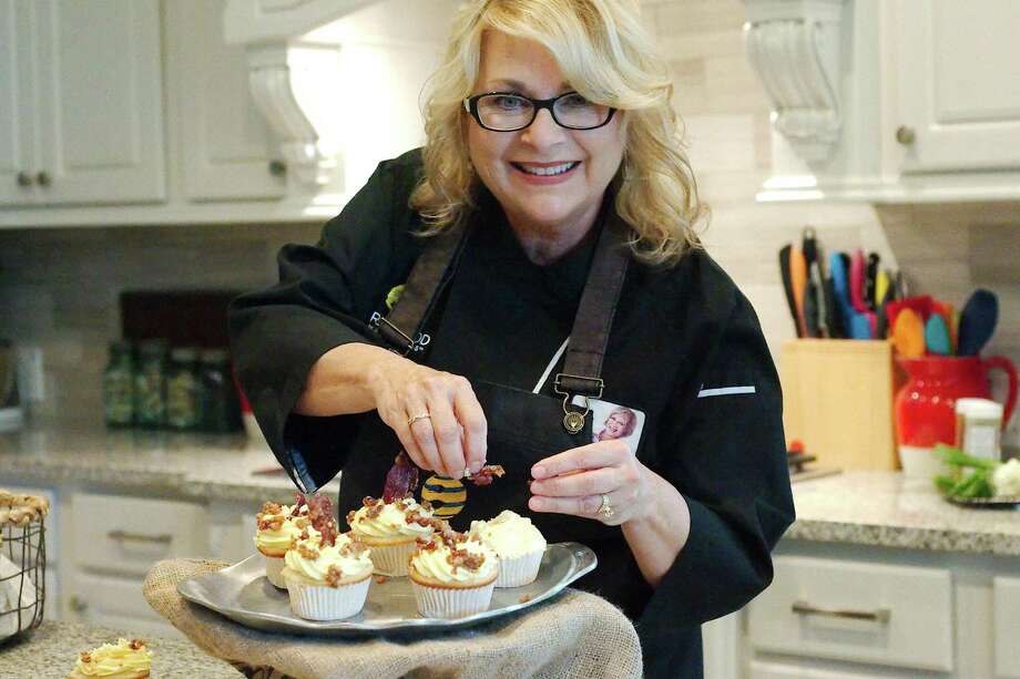 2017 Bacon World Champion Rebecka Evans adds the finishing touch, pecan bacon candy, to a her Bacon Bourbon Cupcakes. Photo: Kirk Sides / Houston Chronicle / © 2018 Kirk Sides / Houston Chronicle
