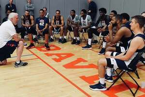 A set of photos shared across the Spurs' official social media pages show Popovich speaking to Team USA , watching practice and laughing with Jeff Van Gundy.