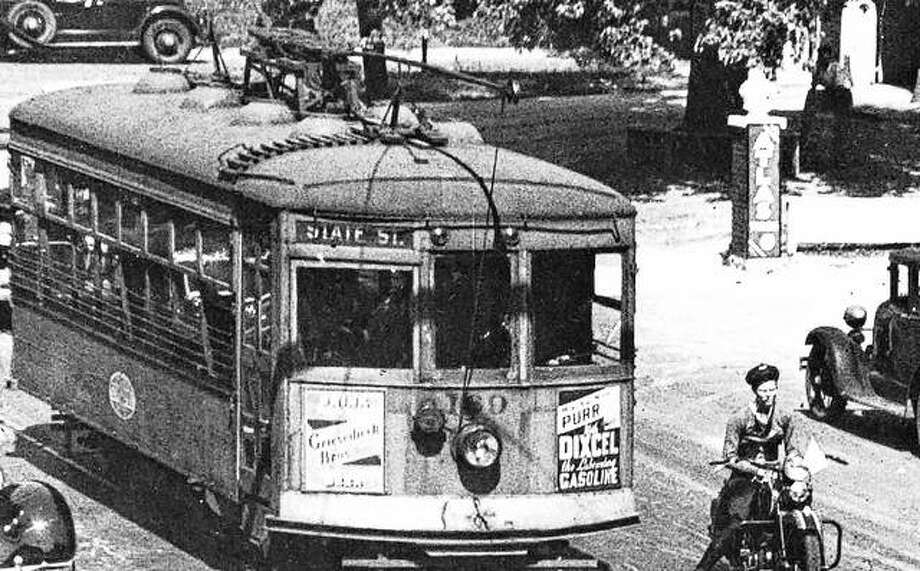 A 1936 scene in Upper Alton shows the electric streetcar, with advertising placards, making the turn on to Washington Avenue. The College Avenue fire station is barely visible on the right. Photo:     File Photo