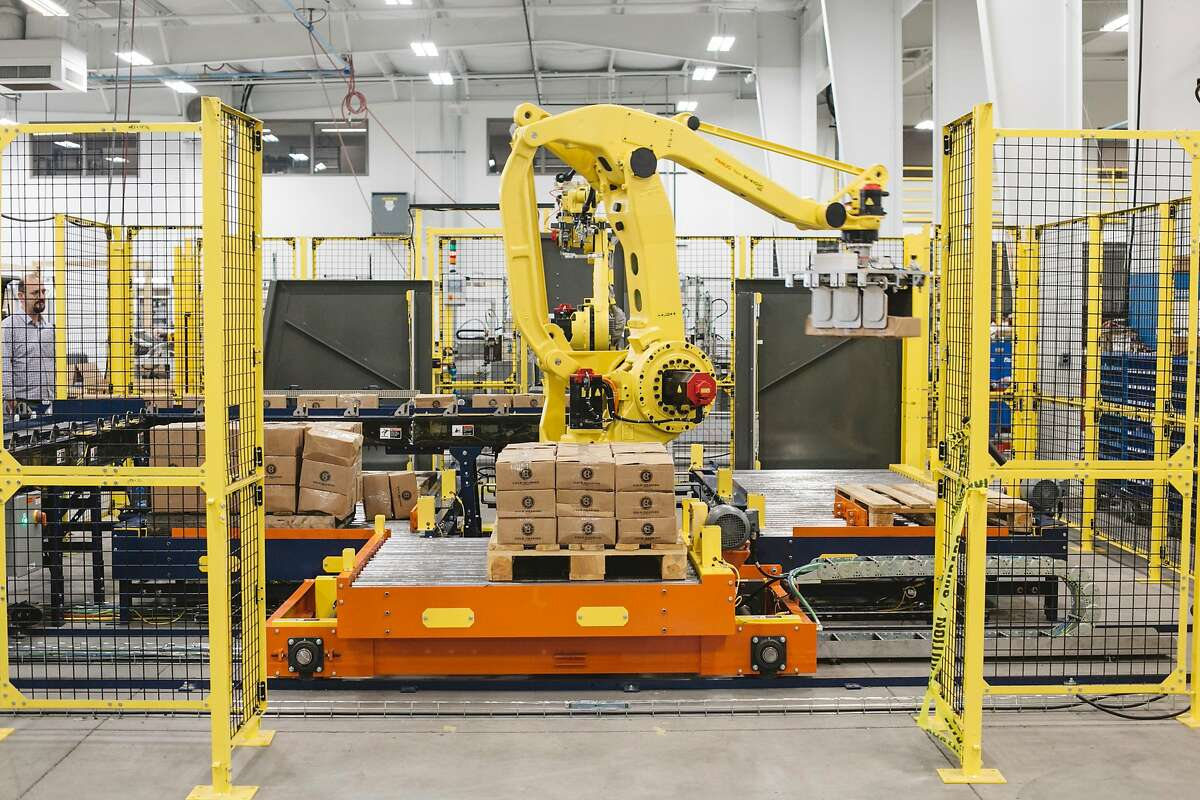 A robot loads boxes onto pallets for shipping at APT Manufacturing Solutions in Hicksville, Ohio, May 10, 2018. APT has begun offering apprenticeships, covering the cost of college for its workers, and three years ago it started teaching manufacturing skills to high school students. (Andrew Spear/The New York Times)