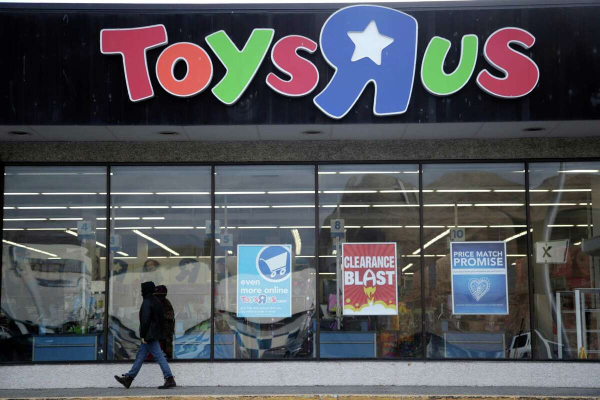This Jan. 24, 2018, photo shows a person walking near the entrance to a Toys R Us store, in Wayne, N.J. Toys R Us is closing its last U.S. stores by Friday, June 29, the end of a chain known to generations of children and parents for its sprawling stores, brightly colored logo and Geoffrey the giraffe mascot.