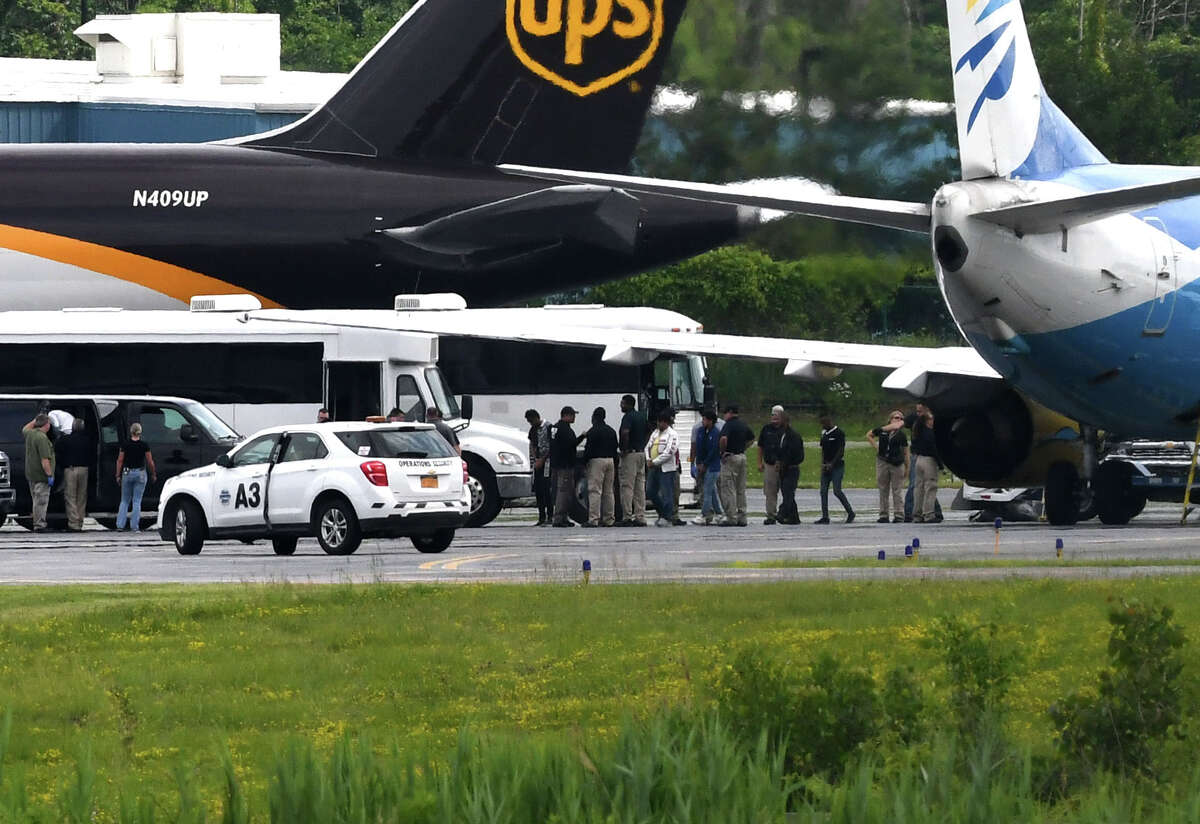 Immigrant men are escorted off a U.S. Immigration and Customs Enforcement jet fromArizona at Albany International Airport during their transport to Albany County Jail on Thursday afternoon, June 28, 2018, in Colonie, N.Y. The jail has taken in 235 immigrants who are being detained on immigration charges. None of them were separated from families according to jail officials. (Will Waldron/Times Union)