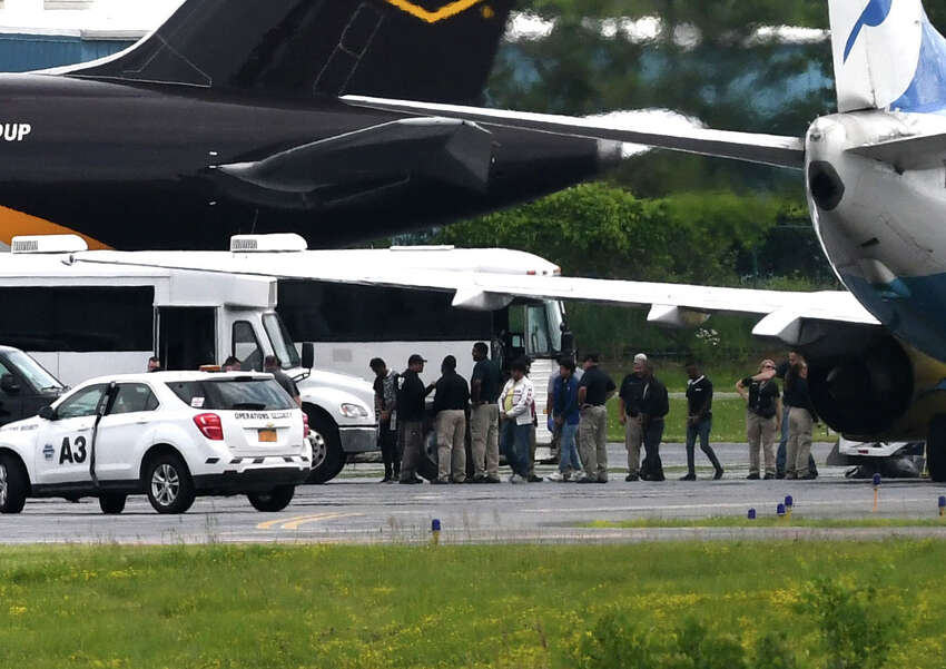 Immigrant men are escorted off a U.S. Immigration and Customs Enforcement jet from Arizona at Albany International Airport during their transport to Albany County jail on Thursday afternoon, June 28, 2018, in Colonie, N.Y. The jail has taken in 235 immigrant men who are being detained on immigration charges. None of them were separated from families according to jail officials. (Will Waldron/Times Union)