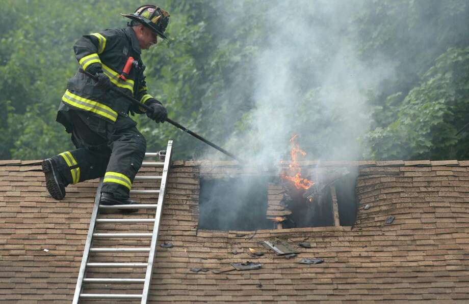Norwalk firefighters battle an attic blaze at 32 Thistle Court that was caused by a lightening strike Thursday, June 28, 2018, in Norwalk, Conn. Photo: Erik Trautmann / Hearst Connecticut Media / Norwalk Hour