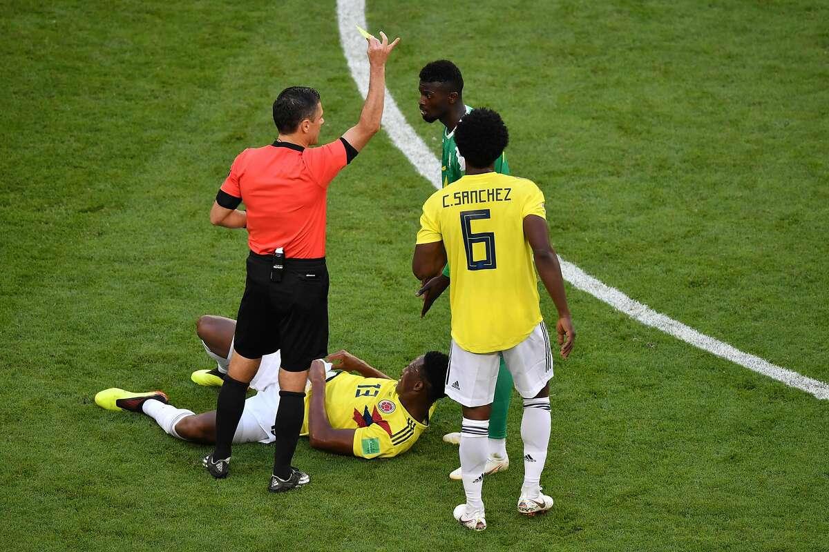 Serbian referee Milorad Mazic gives a yellow card to Senegal forward Mbaye Niang during the a World Cup match at the Samara Arena.