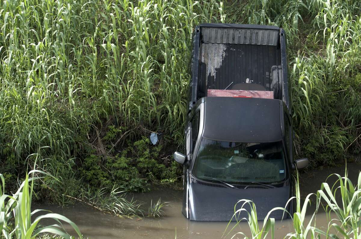 Houston police officers investigate the discovery of a pickup truck in an east Houston bayou Thursday, June 28, 2018.