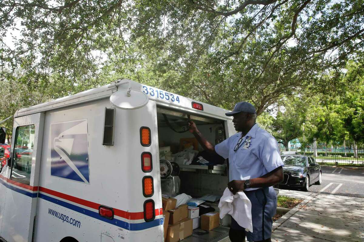In this June 14, 2018, file photo, Elston Bradshaw, a mail carrier for the United States Postal Service closes a mail truck door after delivering mail to an apartment complex in Aventura, Fla. (AP Photo/Brynn Anderson, File)