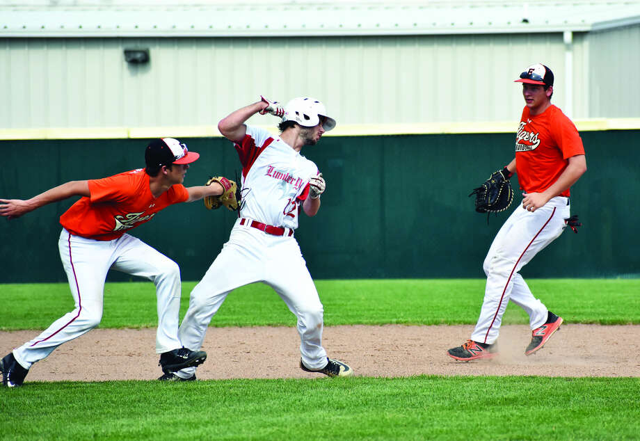 Edwardsville's Logan Cromer tags out the runner to end a pickle with Matt Stopka to the right.