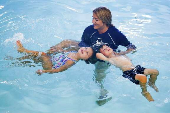 """Houston Swim Club owner Tammy Schoen helps teach Emma Courtney, 4, left, and Nolan Neeley, 3, right, safety swimming techniques, like how to float, Monday, June 11, 2018 in Houston. """"We teach this way so that if they ever fall into a pool, they are better equipped to save themselves,"""" Schoen said. Emma and Nolan were both recipients of swim lesson scholarships from the Judah Brown Project, which aims to teach swimming safety and provide funding for swimming lessons. The Judah Brown Project was founded after three-year-old Judah Brown died in a drowning accident at an apartment pool two years ago. (Michael Ciaglo / Houston Chronicle)"""