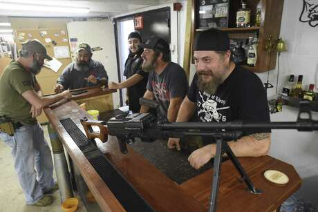 Mike Mihalski, right, friends and workers gather around the counter at Sons of Liberty Gun Works.