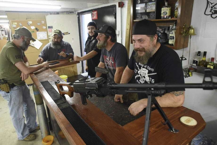 Mike Mihalski, right, friends and workers gather around the counter at Sons of Liberty Gun Works. Photo: Billy Calzada /San Antonio Express-News / San Antonio Express-News