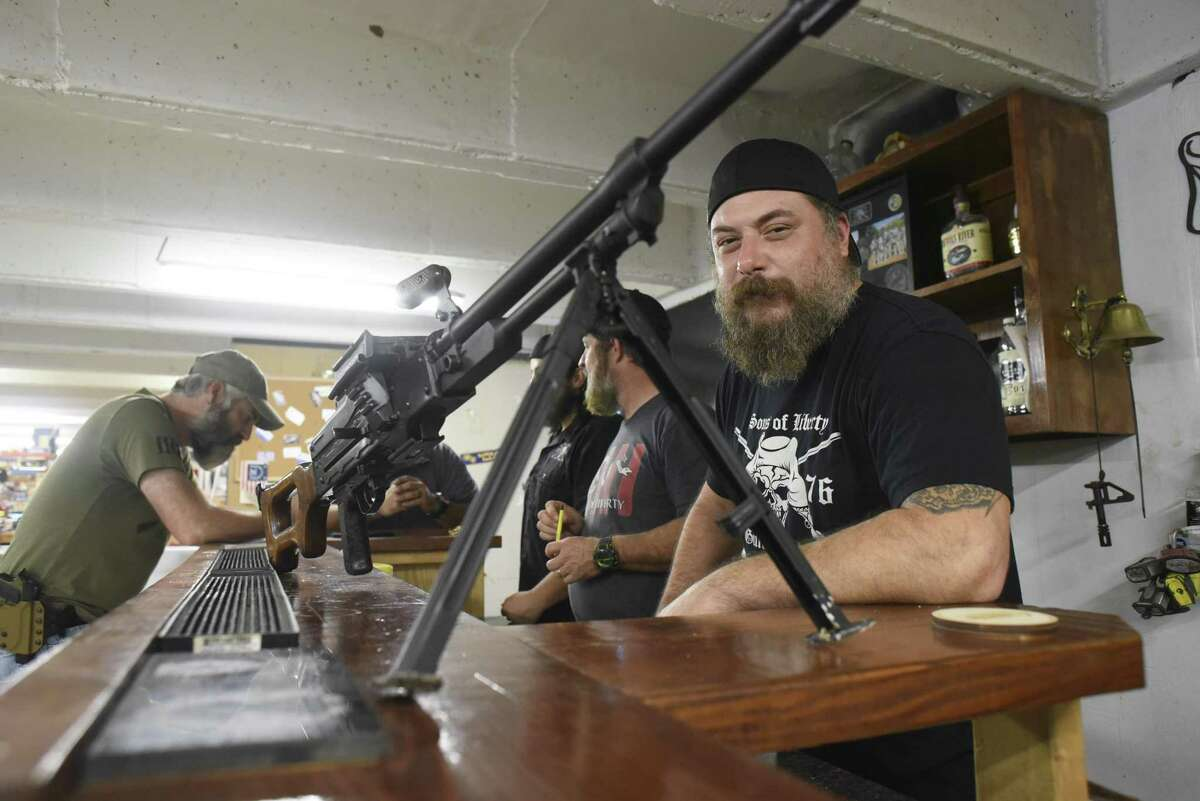 Mike Mihalski, right, co-owner of Sons of Liberty Gun Works stands at the counter near a PKM belt-fed machine gun.