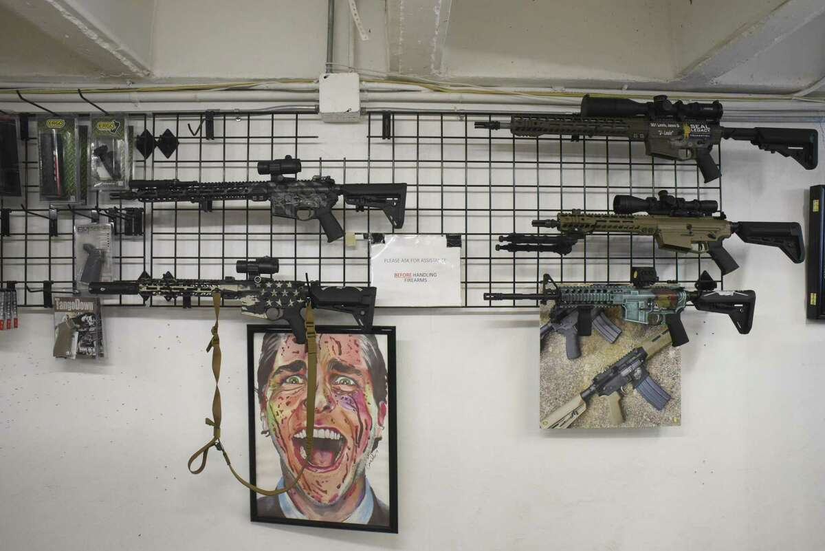 """Various guns are displayed on a wall at Sons of Liberty Gun Works. The artwork is titled, """"Ode to Patrick Bateman."""""""