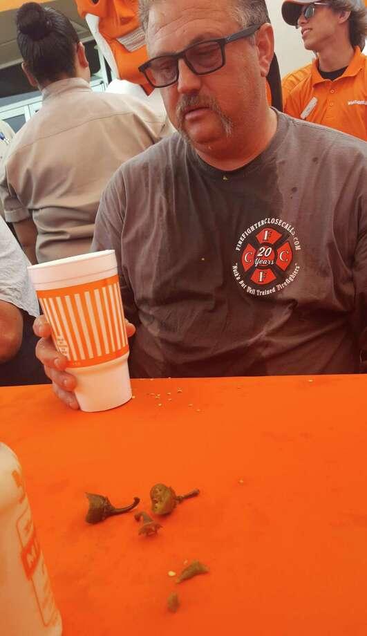 "Schertz firefighter Carl Berghofer looks slightly stunned after he ate 12 jalapenos in 60 seconds during the Cibolo Police vs. Schertz Fire departments' ""Bring The Heat"" jalapeno-eating contest June 21. Photo: Jeff B. Flinn / NE Herald"