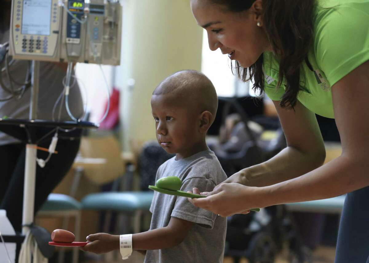 Logan Ibarra, 4, balances walking with an object on a spoon with Olympian long jumper Yvonne Treviño Hayek, of Mexico, in a ?