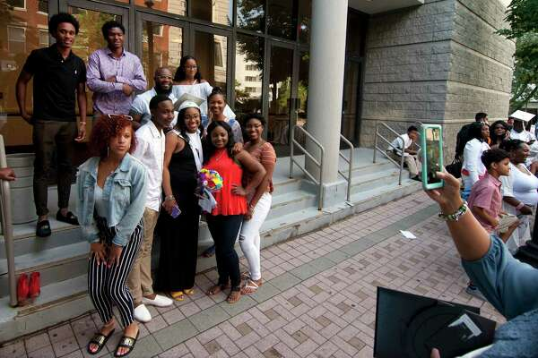 Relatives pose for photos with graduate Shanyce Thomas after Capitol Prep Harbor School's 3rd Annual Commencement Ceremony at the Holiday Inn in downtown Bridgeport, Conn., on Thursday June 28, 2018.
