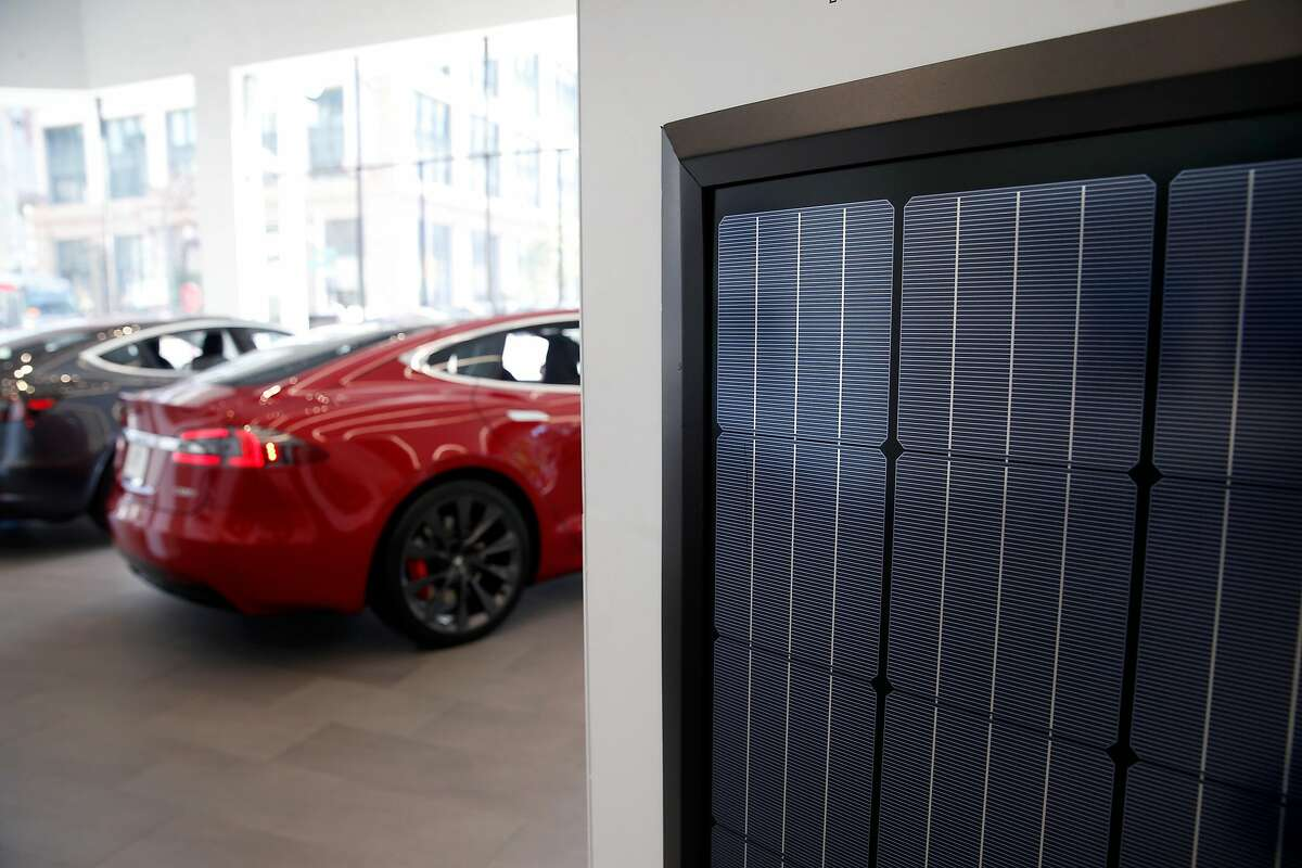 A solar panel is displayed near a Model 3 and a Model S at the Tesla store in San Francisco, Calif. on Thursday, June 28, 2018. Tesla is selling solar products from recently acquired SolarCity directly in its automobile showrooms.