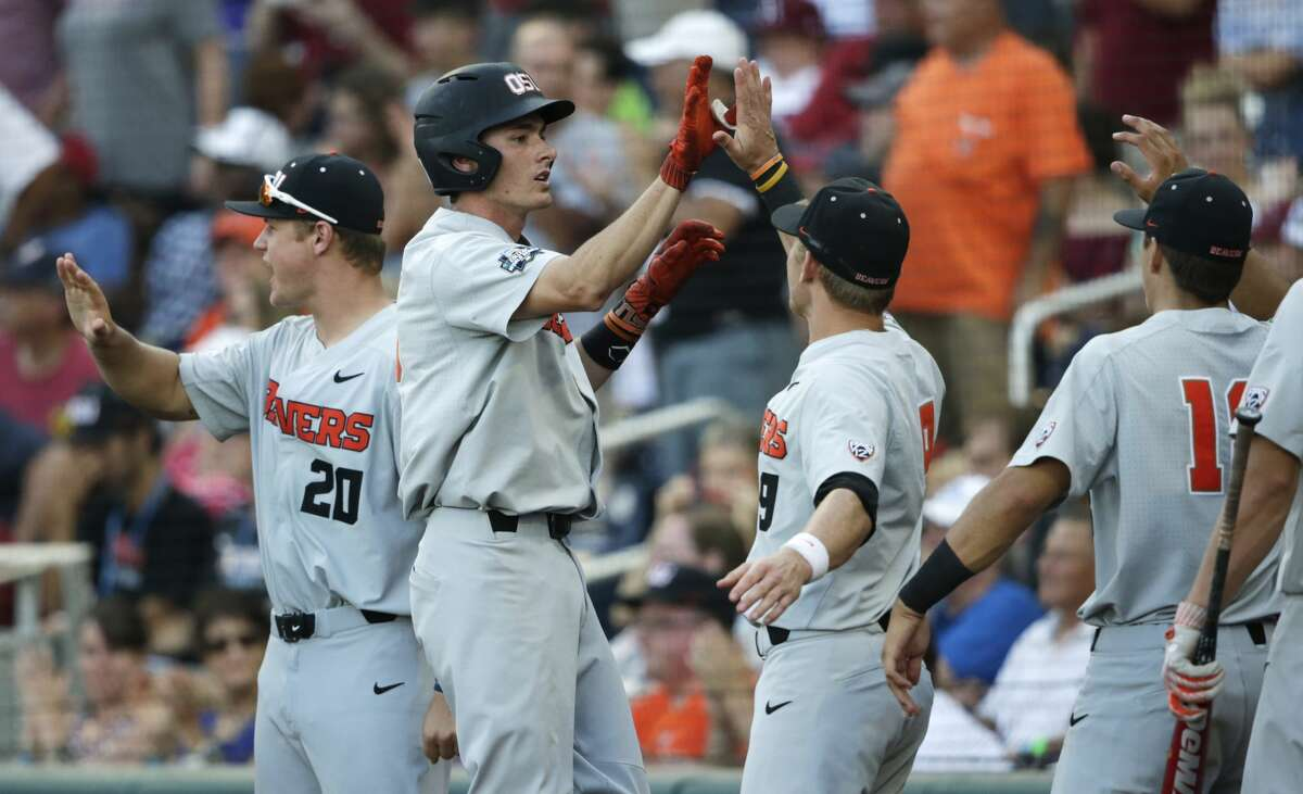 Oregon State third baseman Michael Gretler, second from left, is greeted by teammates after he hit a sacrifice fly to score Adley Rutschman during the fifth inning against Arkansas in Game 3 of the NCAA College World Series baseball finals, Thursday, June 28, 2018, in Omaha, Neb. (AP Photo/Nati Harnik)