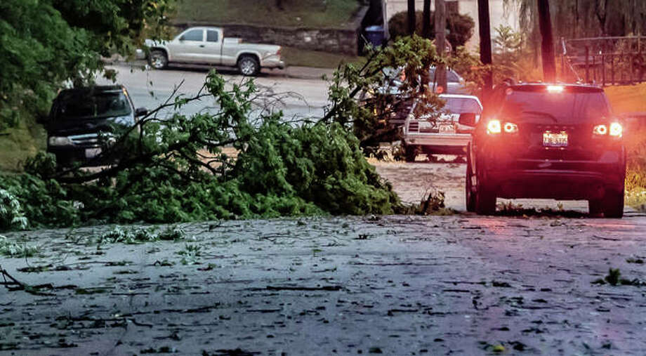 A vehicle carefully passes over a felled tree and over debris on Dry Street in Alton Thursday evening.