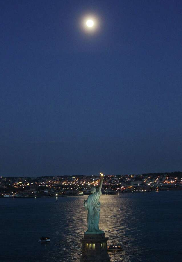 The Statue of Liberty beneath a rising moon. Photo: Mario Tama / Getty Images / 2011 Getty Images