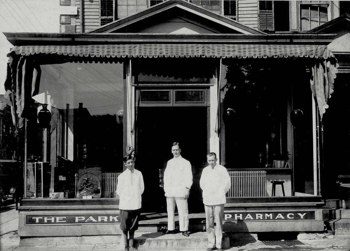 Courtesy of Leo Hulton SPECTRUM/Gif Noble, center, the druggist and owner of the Park Pharmacy, poses to be photographed with two young men, identity unknown, in the early years of the business, likely the late 1920s or early 1930s. The Park Pharmacy was located at the corner of Main and Bank streets in New Milford, later to be succeeded on the same site by the Slone Pharmacy and now the New Milford Pharmacy. The United States Hotel had anchored the busy corner site along the Village Green for many years. For Way back When 7/6/18