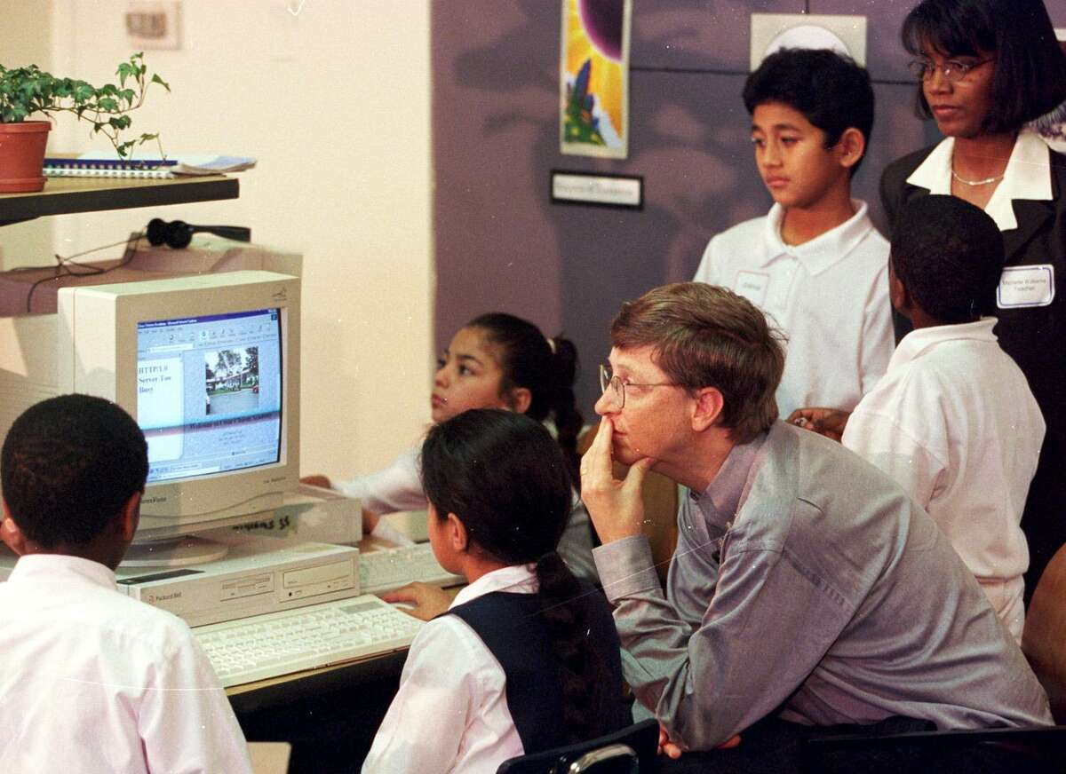 Bill Gates looks over computer work by students in a third-grade classroom 20 years ago.