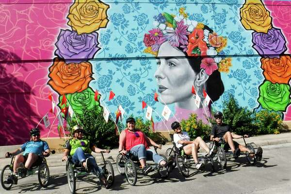 A group taking a trip guided by San Antonio Bike Tours pauses in front of a mural at the Fiesta store.