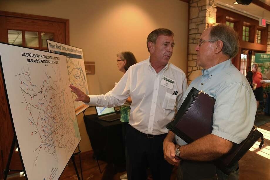 Jim Greeson, a Harris County Flood Control District Professional Engineer, chats about the HCFCD Rain & Stream Gage Location Map with Jim Robetson, Chairman of the Cypress Creek Flood Control Coalition during the HCFCD Bond Program Information & Community Engagement meeting at the Big Stone Lodge At Dennis Johnston Park in Spring on June 27, 2018. (Jerry Baker/For the Chronicle) Photo: Jerry Baker, Freelance / For The Chronicle / Freelance