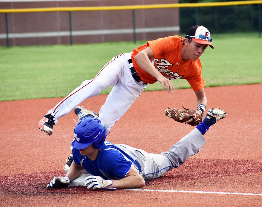 Edwardsville third baseman Weston Slemmer, top, tumbles over a Midwest Dodgers runner sliding into third base for a stolen base during Friday's game at the EHS junior varsity field.
