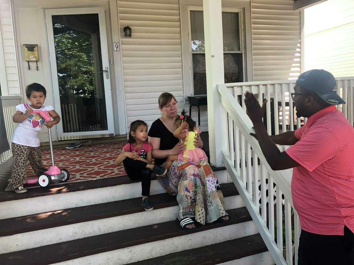 RISSE soccer coach Ali Abdalla speaks with volunteer Renee Bautista at her home. (Massarah Mikati / Times Union)