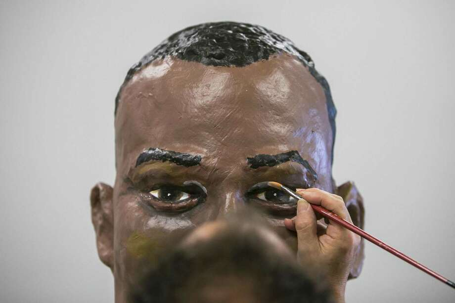 David Ventura paints the final touches on the model of David Robinson's head at the Southwest School of Art. Gigantes, including Robinson, and cabezudos, big-headed figures representing iconic characters, will be featured in a traditional Spanish parade on Saturday at the Pearl. Photo: Josie Norris /San Antonio Express-News / © San Antonio Express-News