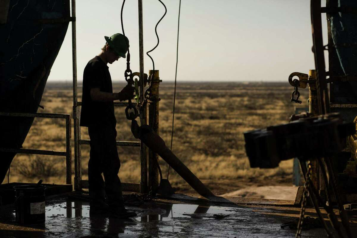 A 2014 photo shows a worker waiting to connect a drill bit on Endeavor Energy Resources's Big Dog Drilling Rig 22 in the Permian basin outside of Midland, Texas. The number of rigs drilling for oil and gas in the U.S. dipped by five this week, continuing a slow decline for most of June.