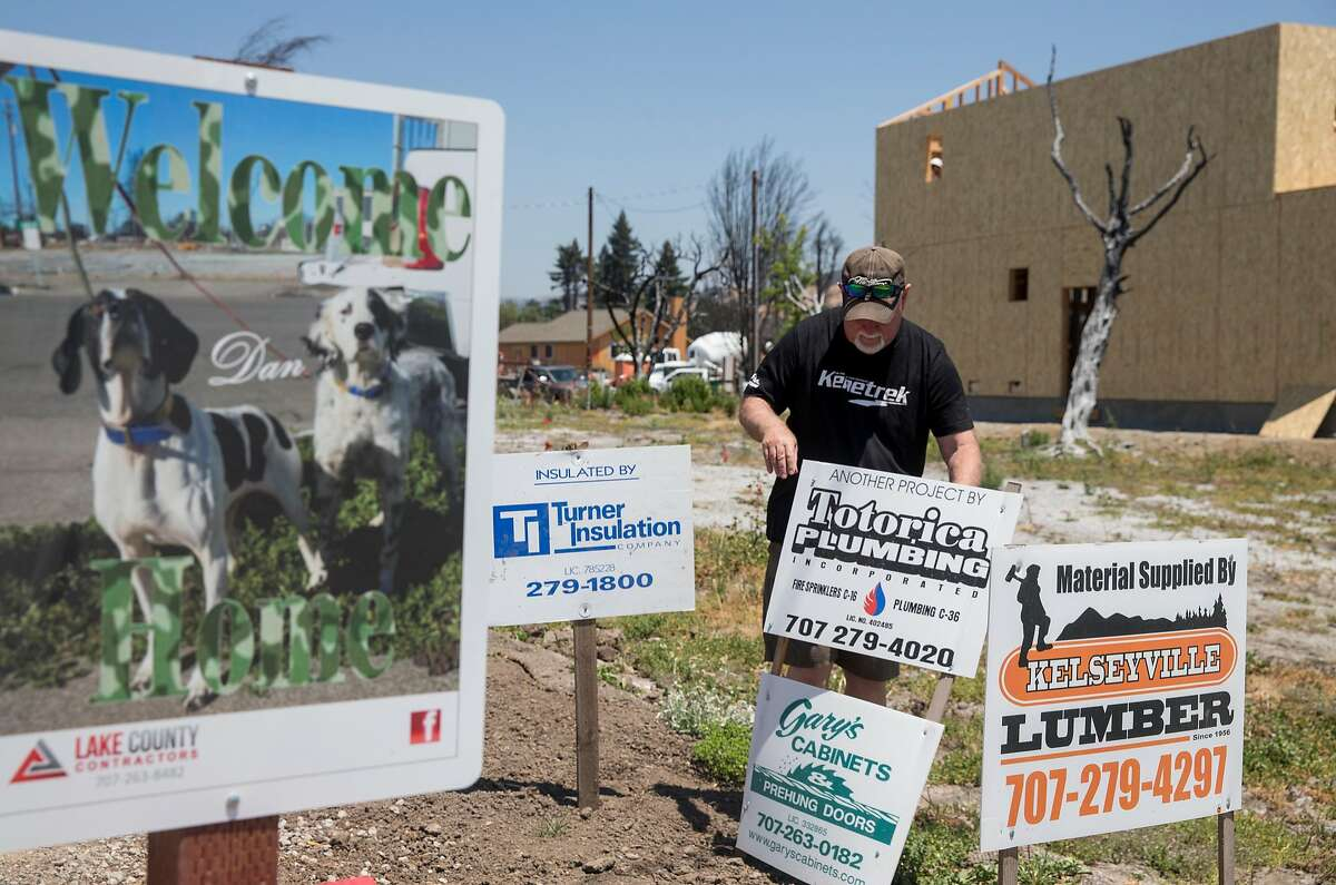 Dan Bradford adjust the contractor signs in the front yard of his newly constructed home built on the site of his former home that was destroyed during the Tubbs Fire in October 2017 in the Coffey Park neighborhood of Santa Rosa, Calif. Friday, June 8, 2018.