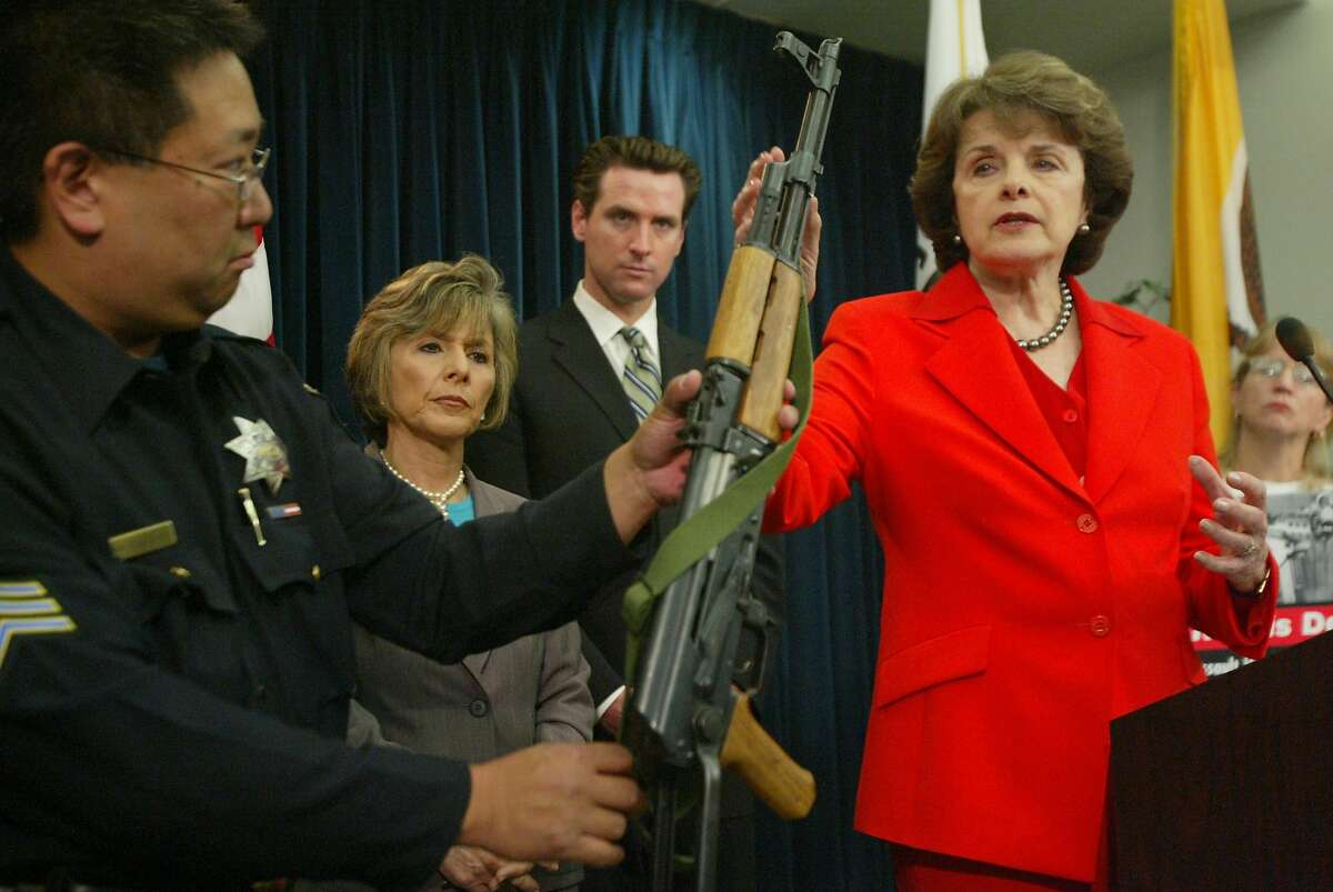 Sen. Dianne Feinstein touches the AK-47 held by San Francisco Police Sgt. Rod Nakanishi as she, Sen. Barbara Boxer and Mayor Gavin Newsom urge renewal of the assault weapons ban in 2004.