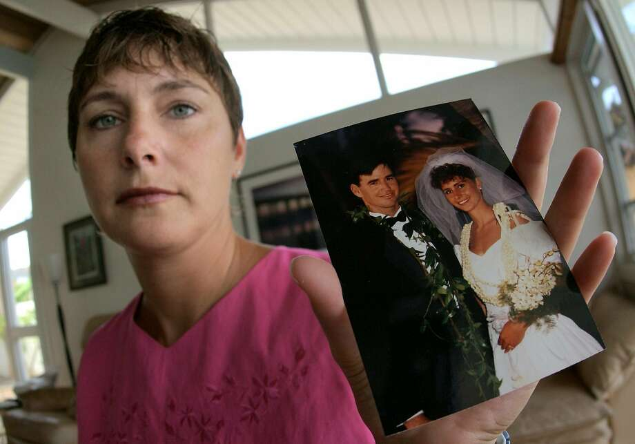 Michelle Hobus, formerly Michelle Scully, holds a wedding picture of herself and her late husband, John Scully, at her home in Hawaii Kai, Hawaii Monday, June 30, 2003. Ten years ago a gunman entered a high-rise in San Francisco and killed eight people, including John Scully, who used his 6-foot-4 frame as a shield to protect his wife. The gunman wordlessly opened the door and shot John six times and Michelle once. (AP Photo/Ronen Zilberman) Photo: Ronen Zilberman / Associated Press 2003