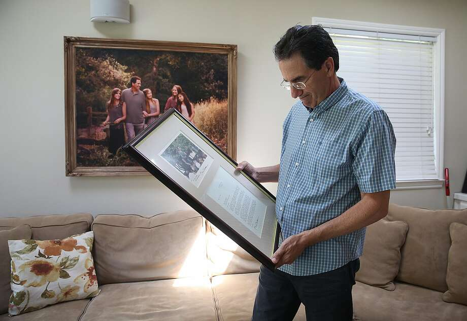 Stephen Sposato with framed letters given to him by president Clinton after the passing of the 1994 Federal Assault Weapons Ban (AWB) which he shows in his living room on Thursday, June 14, 2018 in Lafayette, Calif.  President Clinton mentions Sposato's significant role in passage of assault weapons ban as he listened to Stephen talk of his tragedy while holding his child Meghan beside him. Photo: Liz Hafalia / The Chronicle
