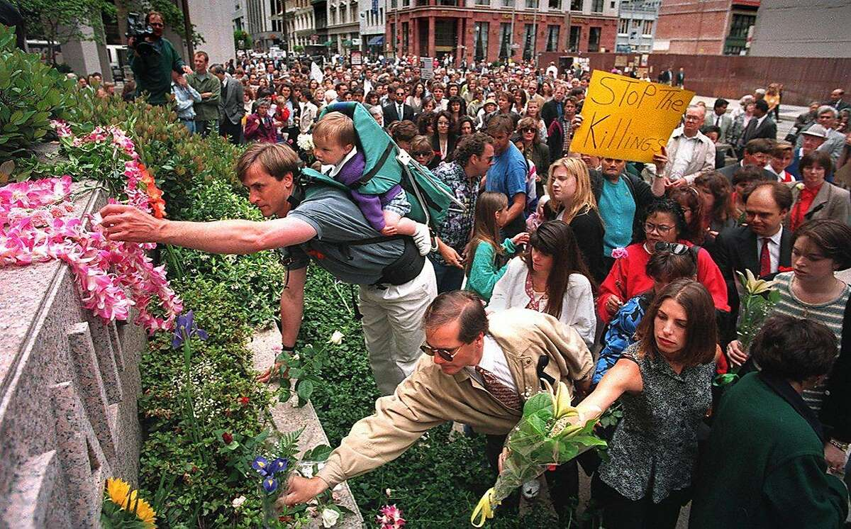 People place flowers at 101 California St. during a memorial march in S.F. on the first anniversary of the 1993 mass shooting.