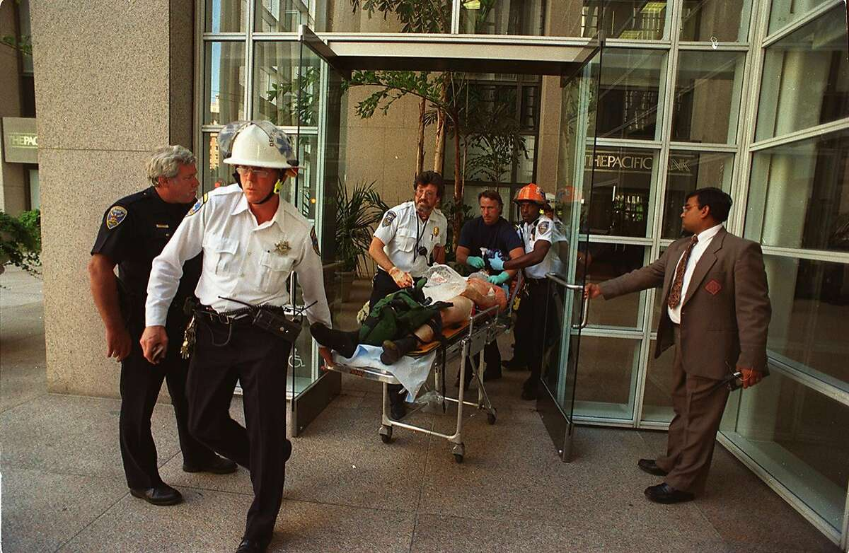 A victim is wheeled out of 101 California St. after a gunman, starting on the 34th floor, opened fire and killed eight people, an act that stunned the city in 1993.