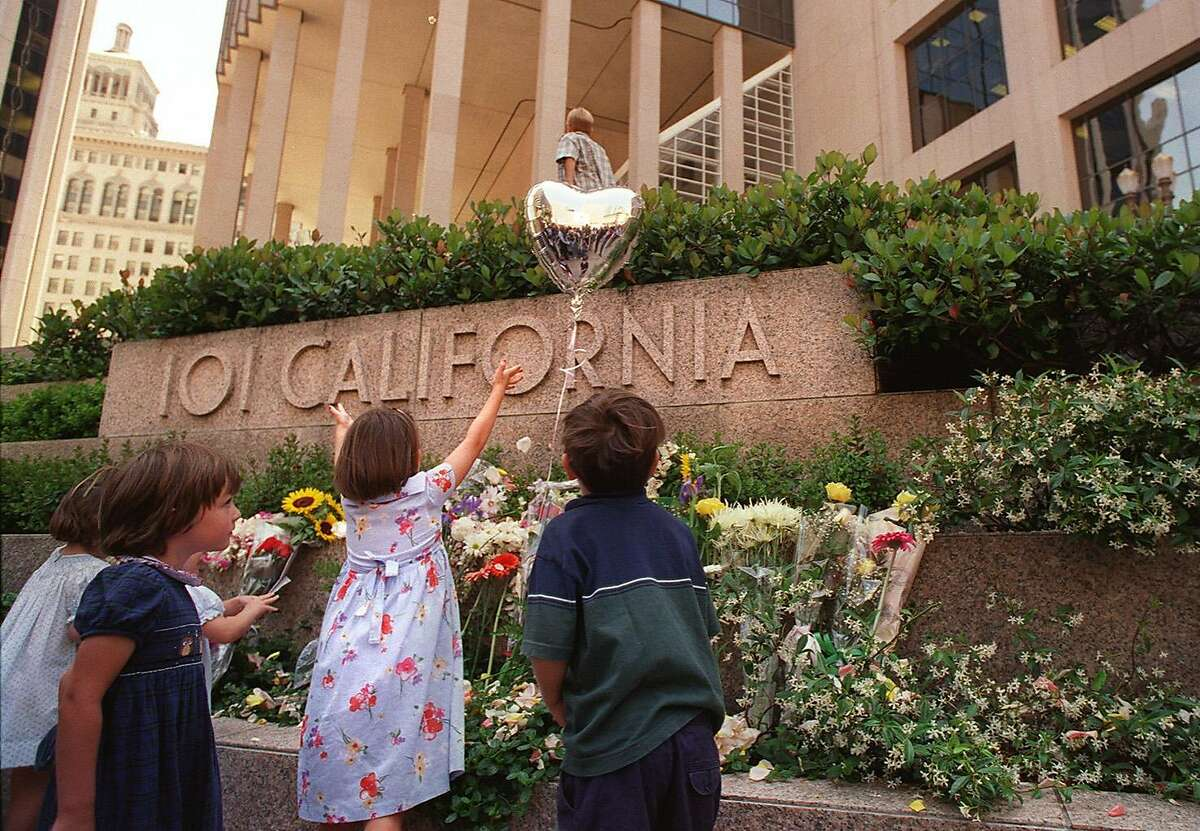 Children of friends and victims of the 101 California St. mass shooting in 1993 look over the array of flowers left during a commemoration in 1998.