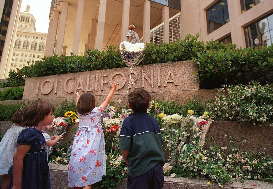 Children of friends and victims of the 101 California St. mass shooting in 1993 look over the array of flowers left during a commemoration in 1998. Photo: Brant Ward / The Chronicle 1998