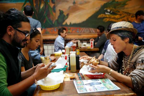 Ajesh Shah (l to r) of San Francisco and Julie Monin of Brazil enjoy burrito dorados during their lunch at La Taqueria on Wednesday, September 10, 2014 in San Francisco, Calif.