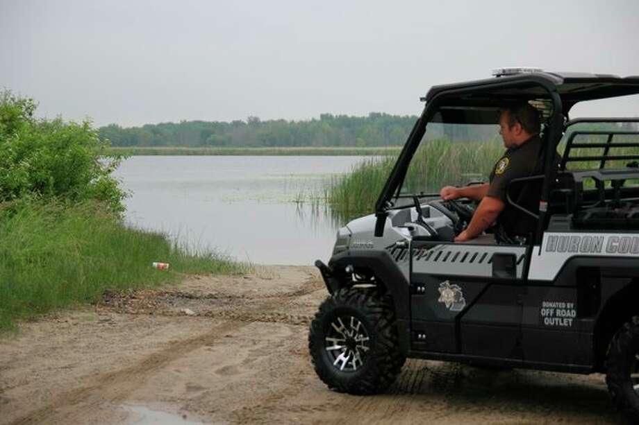 Huron County Sheriff's Deputy Alex Jobes looks out at Rush Lake as he sits in the new Kawasaki MULE, which was donated to the sheriff's office by Off Road Outlet in Bad Axe. The MULE will be used across the county this summer and should be valuable to the department. (Mike Gallagher/Huron Daily Tribune)