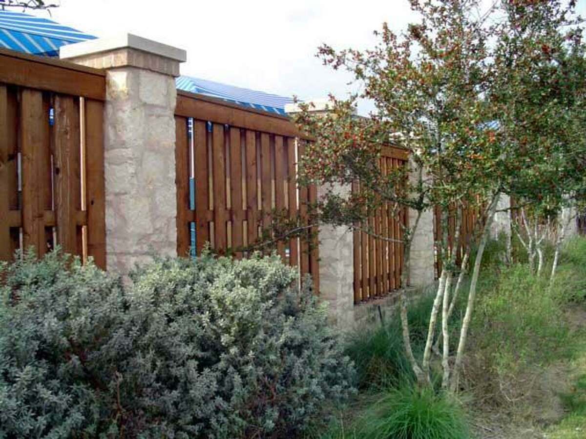 A cedar and stone privacy fence installed by Pecos Fence Co. Inc.