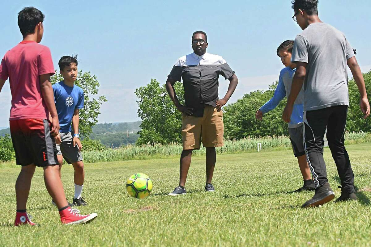 From left, Sakler Moo, 14, Eh Thay, 14, Coach Amjad Abdalla, Klue Thaw, 13, and Bae Rey, 14, practice with some of their soccer team at Hoffman Park. (Lori Van Buren/Times Union)