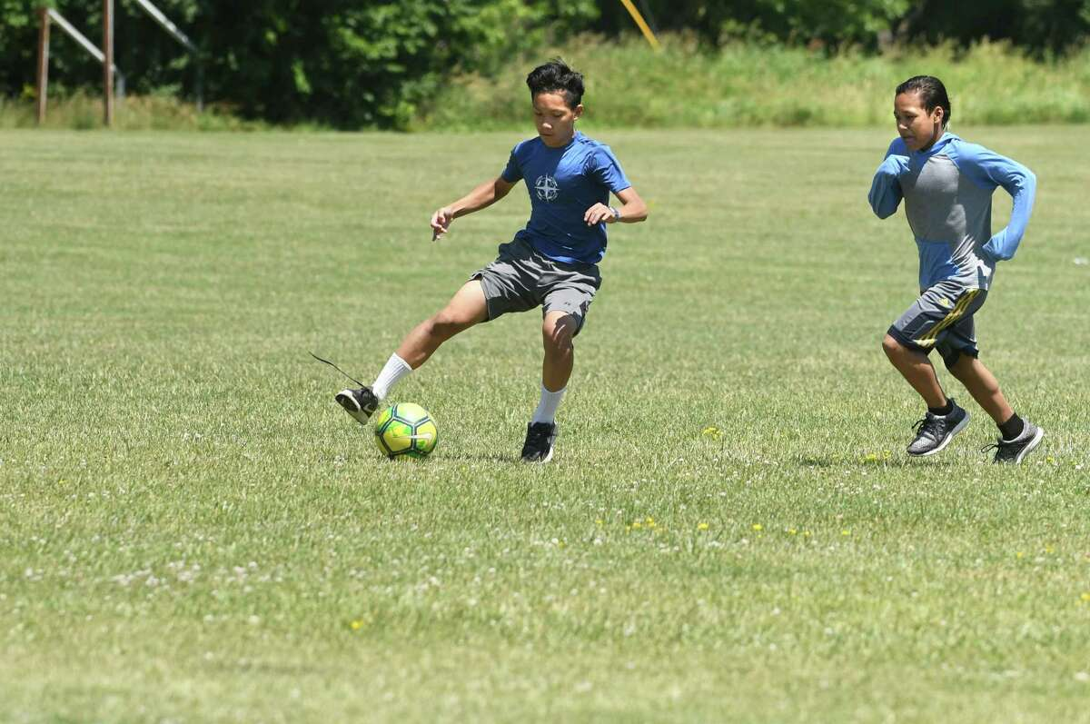 Eh Thay, 14, left, and Klue Thaw, 13, practice with some of their soccer team. (Lori Van Buren/Times Union)